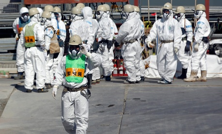 A group of workers wearing protective suits and masks stand next to the No. 4 reactor at Tokyo Electric Power Co. (TEPCO)'s tsunami-crippled Fukushima Dai-ichi nuclear power plant.