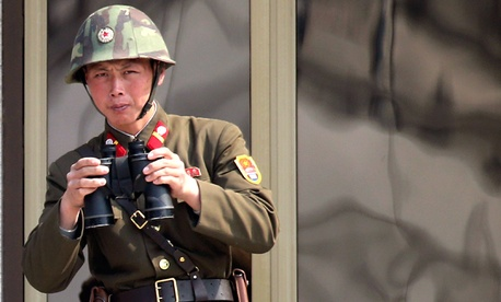 A North Korean soldier watches the South Korean side at the border village of Panmunjom in the demilitarized zone in Korea.