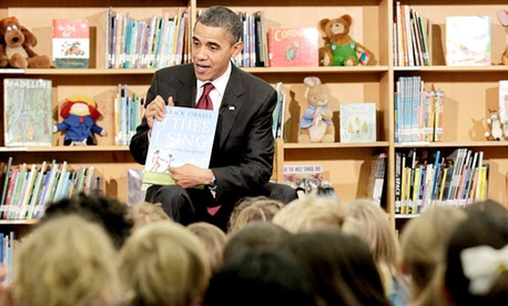 President Barack Obama holds up a book he authored, 'Of Thee I Sing: A Letter to My Daughters', before reading to students at Long Branch Elementary in Arlington, Va.
