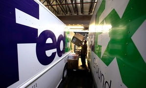 Workers sort packages at a FedEx sorting facility in Kansas City, Mo.