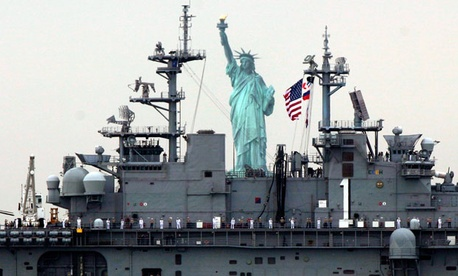 Sailors line the deck of the USS Wasp as she sails by the Statue Of Liberty, in New York, to participate in 2012 Fleet Week activities,