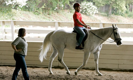 Marine Corps veteran Angel Gomez rides a horse as an instructor looks on during Hippotherapy at the NCEFT, National Center for Equine Facilitate Therapy.