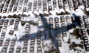 Continental Airlines flight 3306 from Toronto casts a shadow over a snow covered parking lot as it approaches Newark airport in Newark, New Jersey.