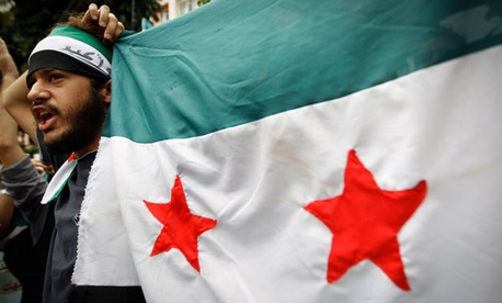 A man holds up a Syrian flag at a recent Malaysian protest of the current Syrian regime.