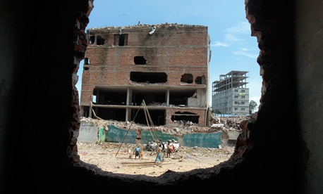Laborers work at the site where a Bangladesh garment-factory building collapsed in April.