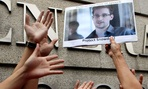 A supporter holds a picture of Edward Snowden, outside the U.S. Consulate General in Hong Kong.
