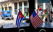 A car drives through Havana, Cuba with American and Cuban flags on its dashboard.
