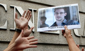 Protestors outside of the U.S. consulate in Hong Kong hold up a photo of Edward Snowden.
