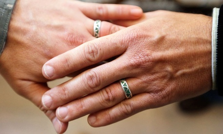 Army Capt. Michael Potoczniak, left, and Todd Saunders, of El Cerrito, Calif., show their wedding rings after they exchanged vows at City Hall in San Francisco.