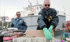 Agents prepare money seized in a drug bust.