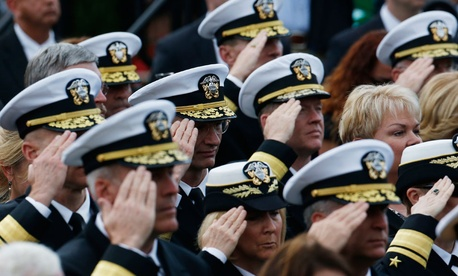 "Navy personnel salute during the playing of ""Taps"" at a memorial service for the victims of the Washington Navy Yard shooting."