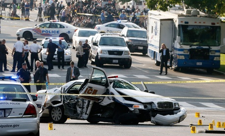 A wrecked Capitol Police car blocks Constitution Avenue NW following a shooting on Capitol Hill in Washington.