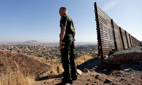 A US Border Patrol agent looks out over Tijuana, Mexico.