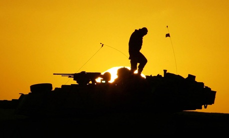 U.S. soldier walks atop his armored vehicle at sunset as he prepares for a nighttime military exercise in the Kuwaiti desert.