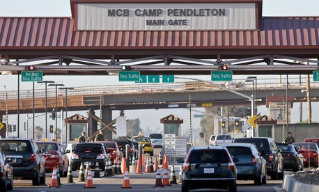 Vehicles file through the main gate of Camp Pendleton Marine Base on Wednesday, Nov. 13, 2013.