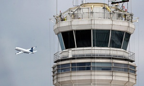 A passenger jet flies past the FAA control tower at Washington's Ronald Reagan National Airport.
