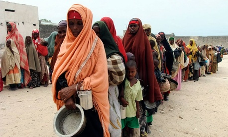 Somali women and children from southern Mogadishu, line up to receive food at a camp in Mogadishu.