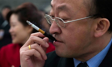 A delegate smokes as he leaves a pre-opening session of the Chinese People's Political Consultative Conference in Beijing in March.