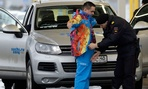 A Russian police officer searches a driver as his vehicle is also screened at an entrance to the Sochi 2014 Olympic Winter Games park.