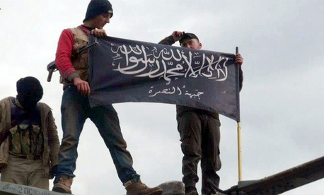 Rebels from al-Qaida affiliated Jabhat al-Nusra waving their brigade flag as they step on the top of a Syrian air force helicopter.