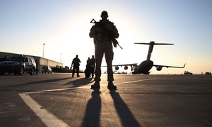 A solider stands guard near a military aircraft in Kandahar, Afghanistan.