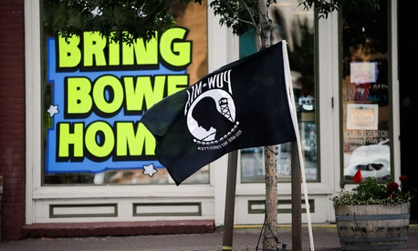 A POW-MIA flag flies in front of a pharmacy displaying a sign in support of bringing home U.S. Army Sgt. Bowe Bergdahl, who is currently being held captive by the Taliban in Afghanistan.