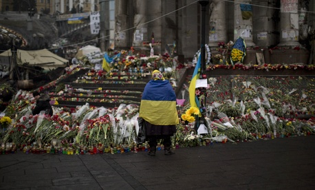 A woman rests by a memorial in Kiev.