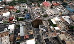 A sinkhole covers a street intersection in downtown Guatemala City, Wednesday, June 2, 2010.