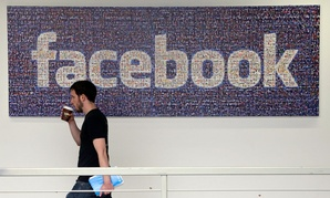 A Facebook employee walks past a sign at Facebook headquarters in Menlo Park, Calif.
