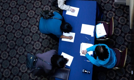 Job seekers line up to sign in before meeting prospective employers at a career fair in Dallas.