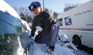 Danny Kim clears snow and ice as he climbs on the hood of his mail delivery truck in January.