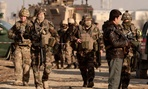 Afghan security forces and U.S. soldiers arrive at the site where a suicide attacker rammed a car bomb into a NATO convoy killing two foreign civilian contractors, in the Afghan capital Kabul, Afghanistan on Feb. 10, 2014.