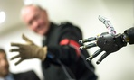 Joint Chiefs Chairman Gen. Martin Dempsey controlling a prosthetic arm during a visit to DARPA