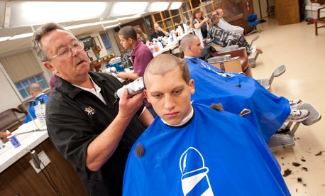 Bill Maynard cuts the hair of Jordan Converse at the U.S. Coast Guard Academy in 2012.