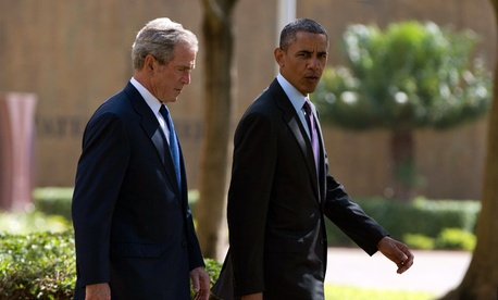 U.S. President Barack Obama, right, walks with former president George W. Bush.