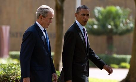 U.S. President Barack Obama, right, walks with former president George W. Bush.