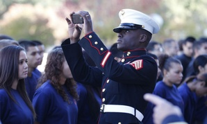 A Marine takes a smartphone photo of military enlistees as they line up before taking their oath in front of Dallas City Hall