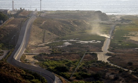 A U.S. Border Patrol vehicle, right, drives along a road running alongside the border structures that separate Tijuana, Mexico, left, from San Diego.