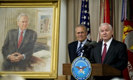 Defense Secretary Robert Gates, right, addresses the audience while former Defense Secretary Donald Rumsfeld looks on during Rumsfeld's portrait unveiling ceremony at the Pentagon, in 2010.