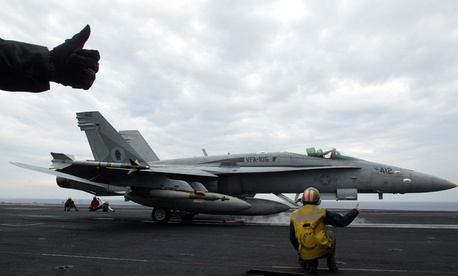 Final checkers give thumbs up to an F/A-18 Hornet on the flight deck of the U.S.S. Harry S. Truman in preparation for a strike operation in Iraq in 2003.