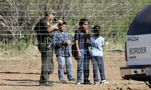 A Border Patrol agent stands on a ranch fence line with children taken into custody in South Texas brush country north of Laredo, Texas.