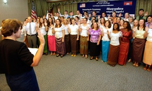 Peace Corps volunteers raise their hands to swear in during a ceremony in Phnom Penh, Cambodia in 2011.