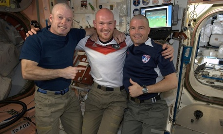 Astronauts Steve Swanson, Alexander Gerst, and Reid Wiseman smile after Gerst shaved the Americans' heads.