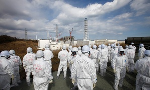 Members of the media wearing protective suits and masks visit Tokyo Electric Power Co.'s tsunami-crippled Fukushima Dai-ichi nuclear power plant during a press tour in Fukushima prefecture, northeastern Japan, Feb. 20, 2012.