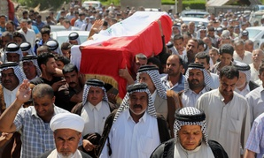 Mourners chant slogans against ISIL while carrying a coffin holding the body of a car-bomb victim, on April 24, 2014.