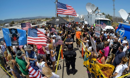 Demonstrators from opposing sides confront each other while being separated by Murrieta police officers, July 4, 2014, outside a U.S. Border Patrol station in Murrieta, Calif.