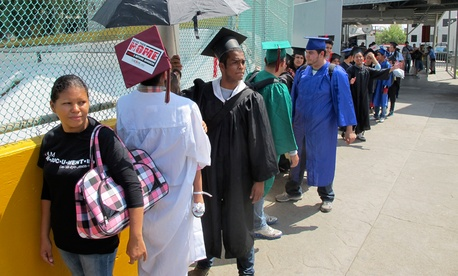 Wearing graduation-style caps and gowns, U.S.-raised immigrants wait on the Mexican side of the international bridge as they try to return to the U.S. from Nuevo Laredo, Mexico in September.