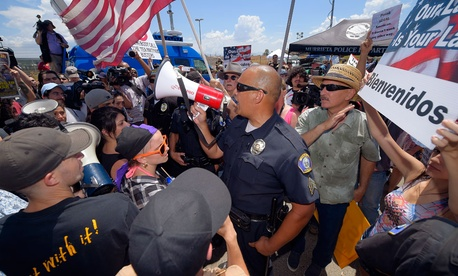 A Murrieta police sergeant talks to demonstrators as they confront each other, Friday, July 4, 2014, outside a U.S. Border Patrol station in Murrieta, Calif.