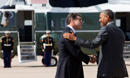 President Barack Obama, right, and Texas Gov. Rick Perry shake hands as Obama arrives in Dallas where they will attend a meeting about the border and immigration together.