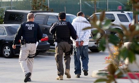 ICE agents take a suspect into custody in California in 2012.